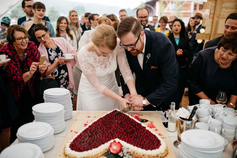 Brautpaar schneidet Erdbeertorte an und Gäste freuen sich im Hintergrund