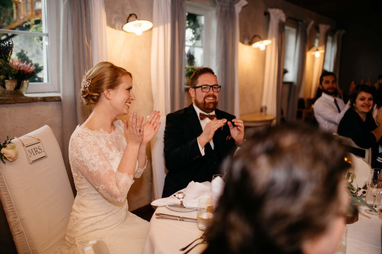 Brautpaar sitzt am Tisch und feut sich