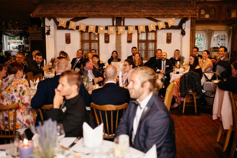 Gäste sitzen an den Tischen und hören dem Braupaar zu