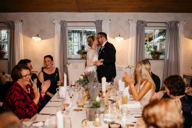 Brautpaar küsst sich am Tisch