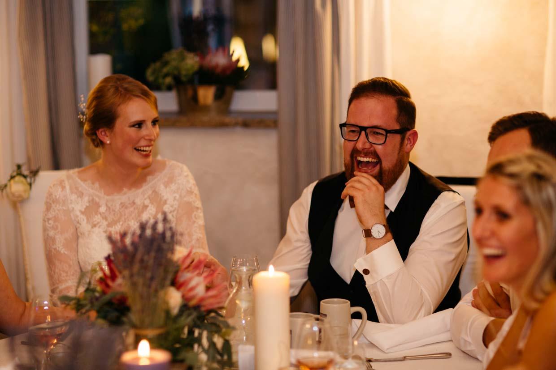Brautpaar sitzt am Tisch und lacht
