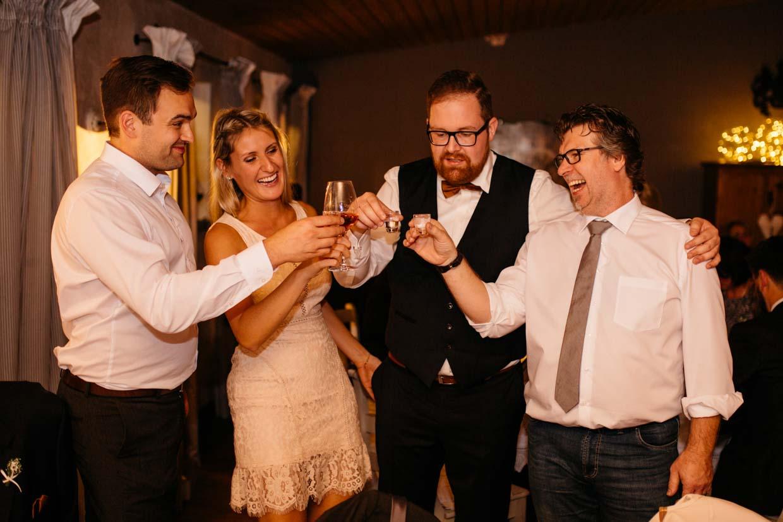 Bräutigam und Hochzeitsgäste stoßen an