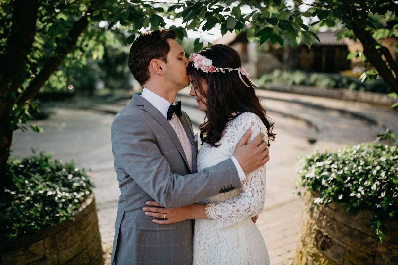 Mann hält seine Partnerin in den Armen und küsst sie auf die Stirn