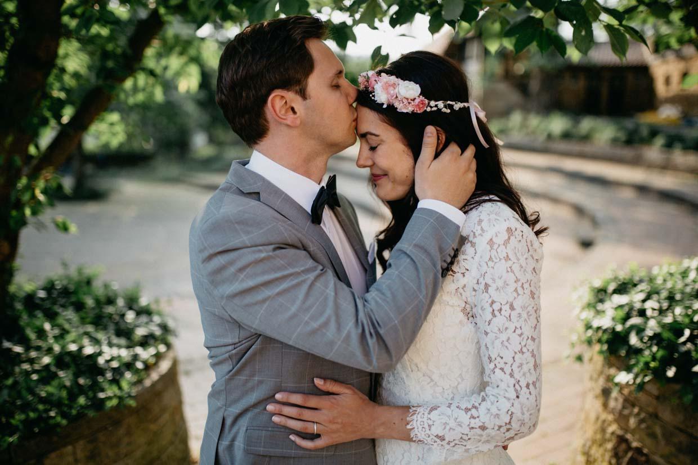 Mann hält sanft den Kopf seiner Partnerin und küsst sie auf die Stirn