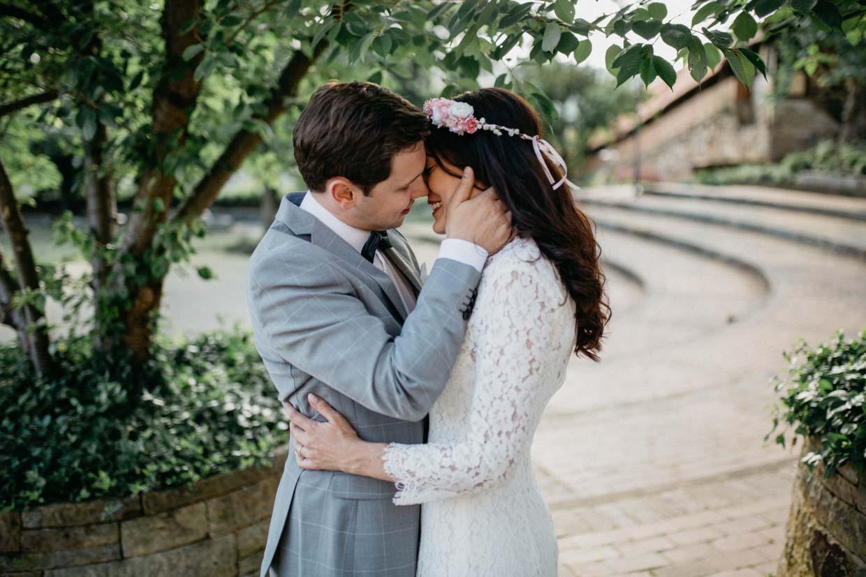 Mann hält sanft den Kopf seiner Partnerin und geht zum Kuss über