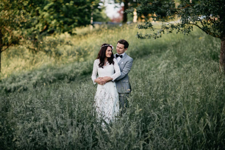 Paar steht im Wiesenfeld und umarmt sich