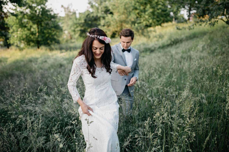 Paar hält Händchen und läuft aus einem Wiesenfeld heraus