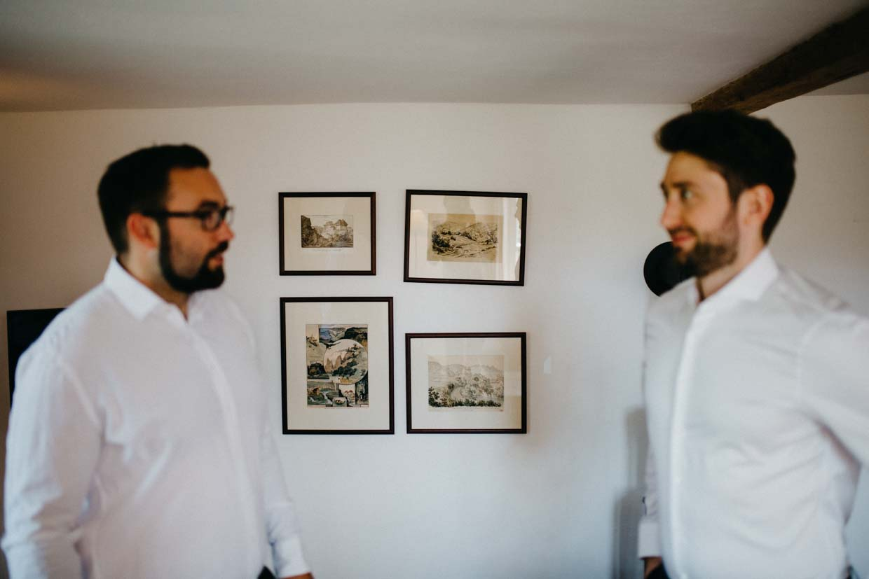 Bräutigam und Trauzeuge stehen vor einer Wand mit Bildern