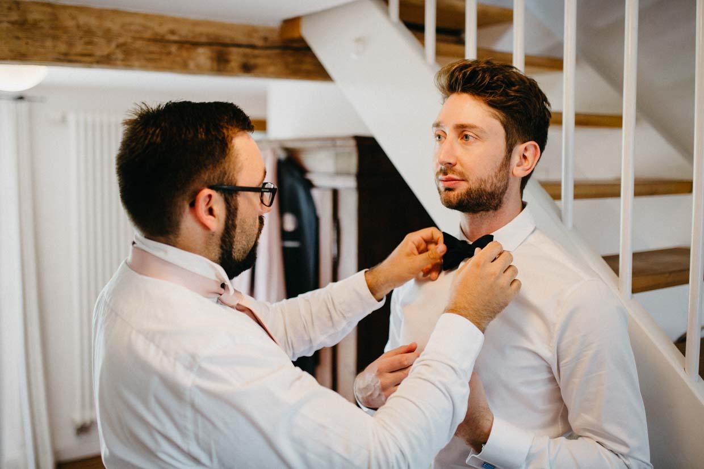 Trauzeuge hilft Bräutigam beim Anziehen der Fliege