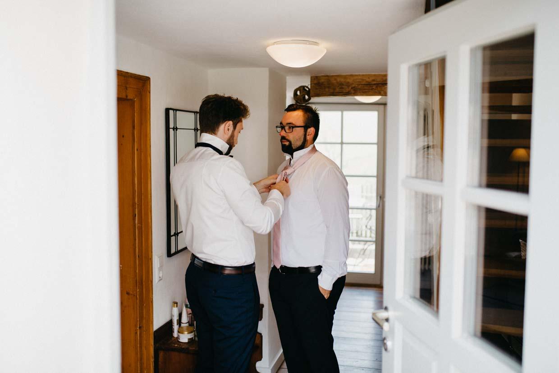 Bräutigam hilft dem Trauzeugen beim Anlegen der Krawatte