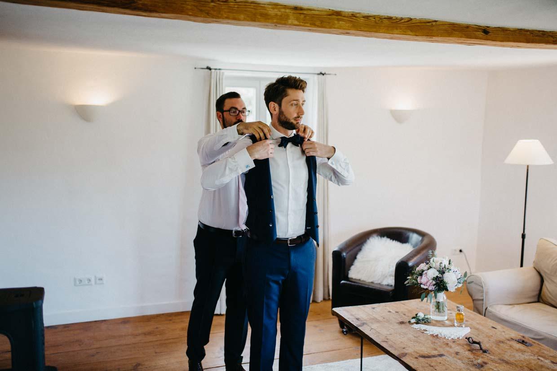 Trauzeuge hilft Bräutigam beim Anziehen der Weste