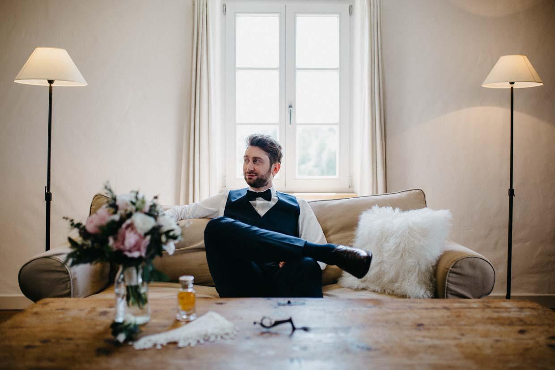 Bräutigam sitzt entspannt auf der Couch