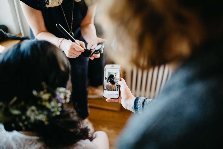 Braut schaut beim Schminken auf das Smartphone