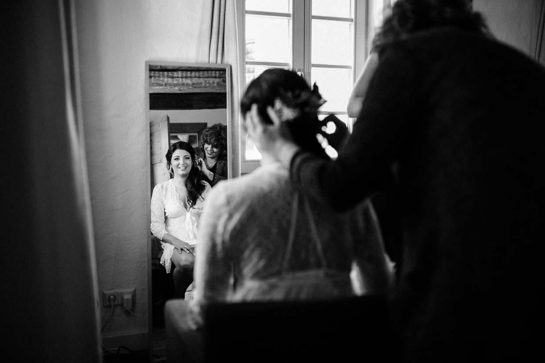 Braut schaut beim Schminken in den Spiegel