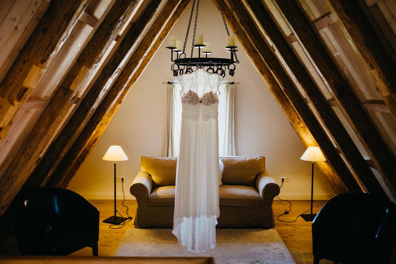 Brautkleid hängt an einem Kerzenleuchter