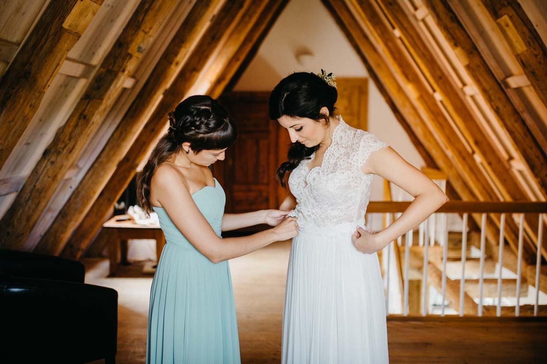Braut und Brautjungfer beim Anziehen des Brautkleides