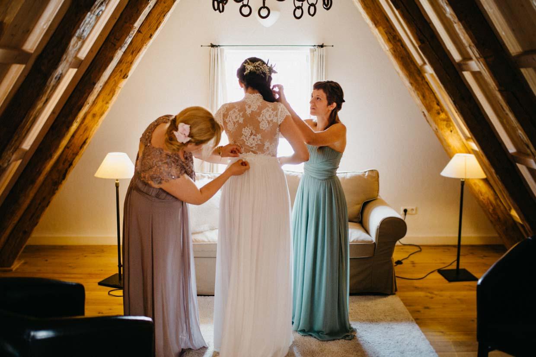 Brautjungfern helfen der Braut beim Anziehen des Brautkleides