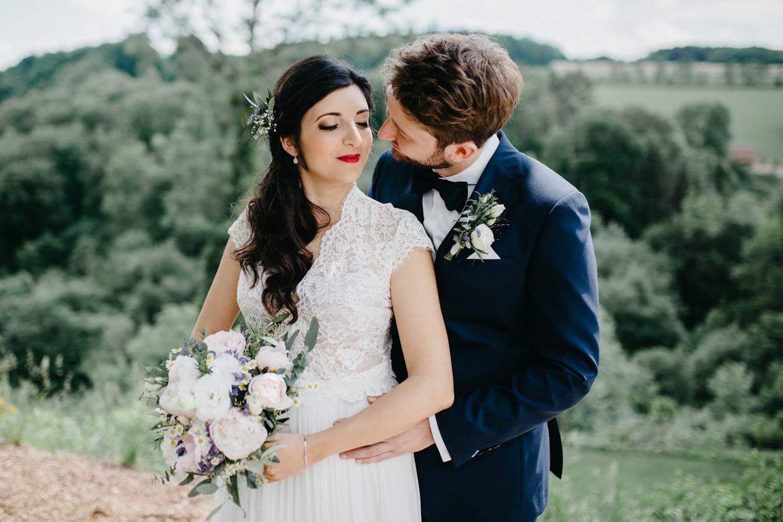 Bräutigam steht beim Brautpaarshooting hinter der Braut und schaut sie an