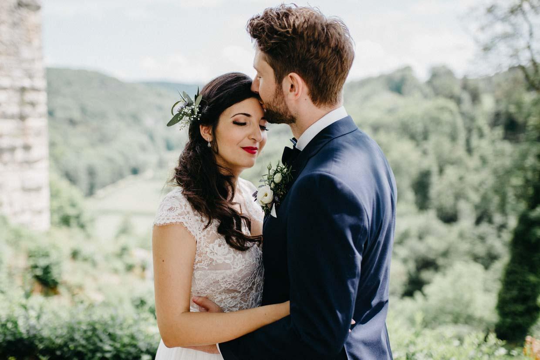 Bräutigam gibt der Braut einen Kuss auf die Stirn