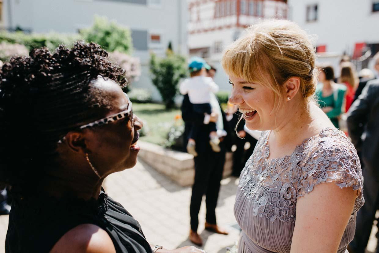 Hochzeitsgäste unterhalten sich und lachen gemeinsam