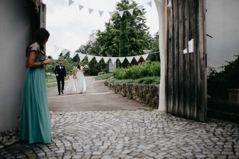 Brautpaar kommt mit Blumenkind an der Hochzeitslocation an