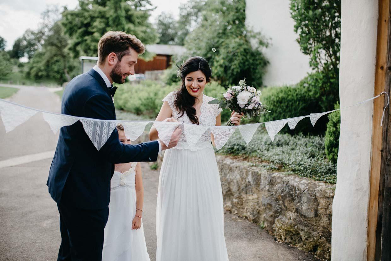Brautpaar schneidet Band zwischen dem Torbogen durch