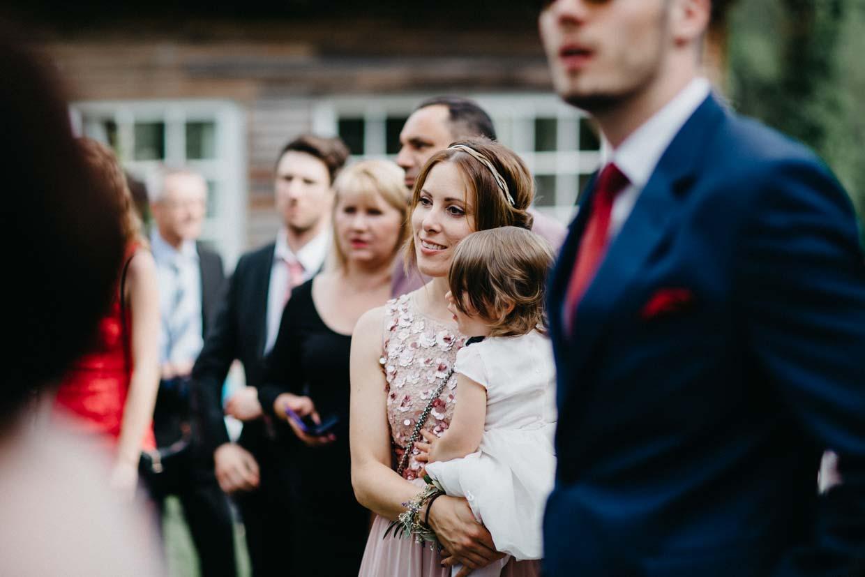 Hochzeitsgast hält Kind auf den Armen und schaut gespannt