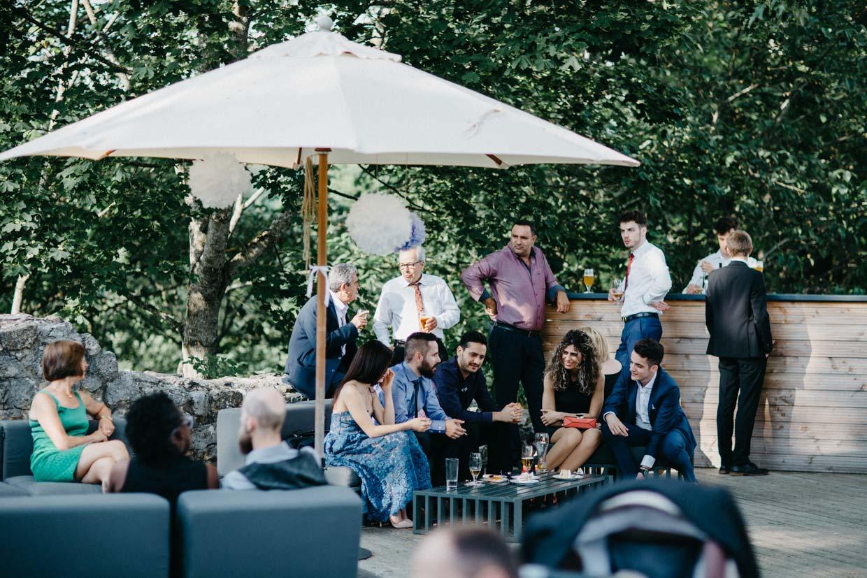 Hochzeitsgäste sitzen auf Loungemöbel und stehen an der Bierbar beim Sektempfang