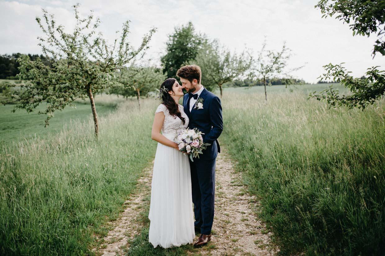 Brautpaar steht sich gegenüber und hält gemeinsam den Blumenstrauß