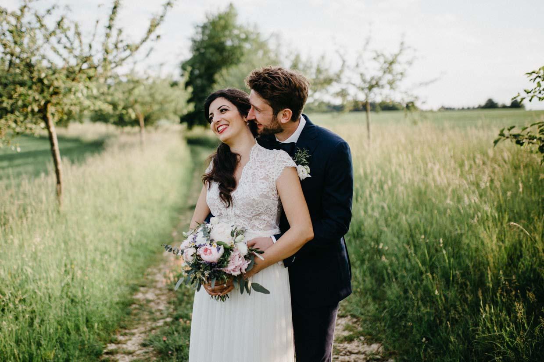 Bräutigam steht hinter der Braut und flüstert ihr etwas ins Ohr