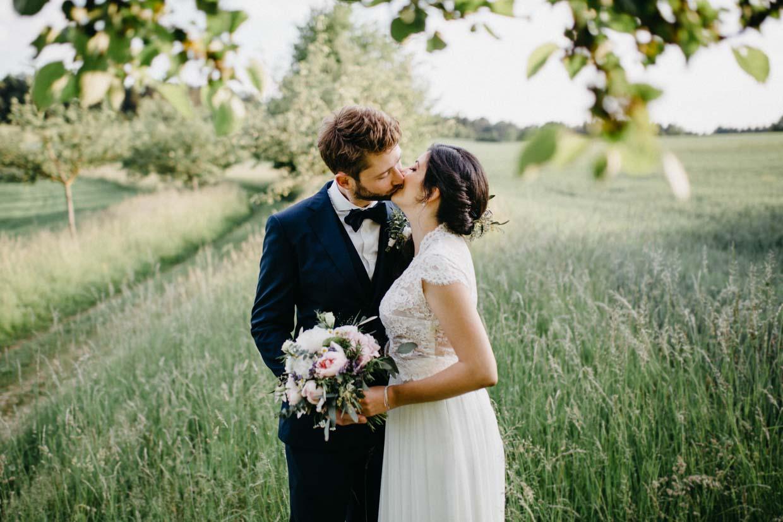 Brautpaar steht unter einem Baum und küsst sich