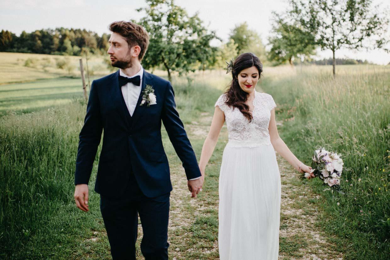 Brautpaar geht gemeinsam einen Feldweg entlang