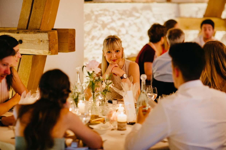 Hochzeitsgast sitzt am Tisch und schaut lieb in die Kamera