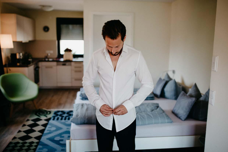 Bräutigam zieht sein Hemd an