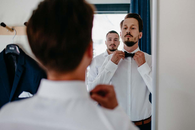 Bräutigam zieht seine Fliege vor einem Spiegel an