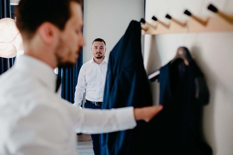 Trauzeuge schaut Bräutigam beim Anziehen zu