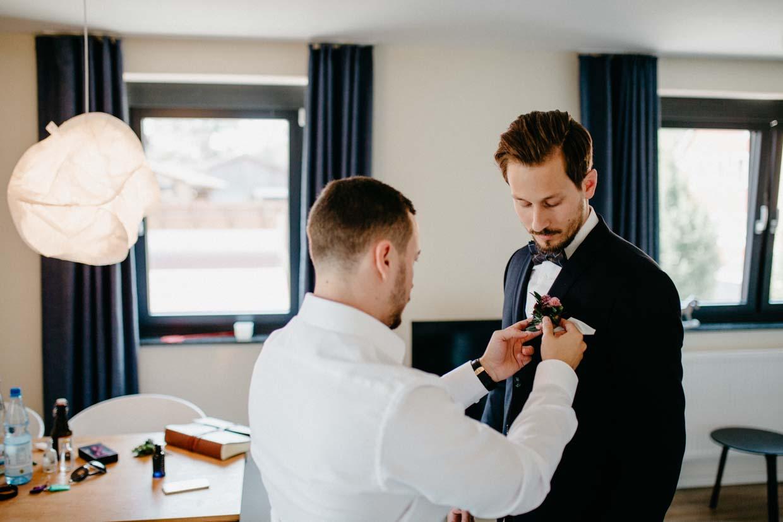 Trauzeuge hilft dem Bräutigam mit dem Blumenanstecker