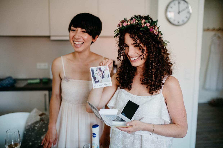 Braut und Trauzeugin lachen beim Getting Ready