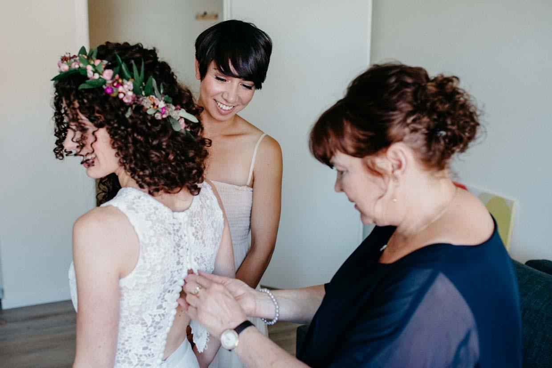 Mutter knöpft der Braut das Brautkleid zu