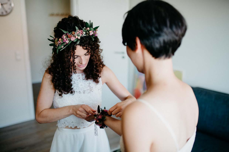 Braut legt der Trauzeugen eine Blumenkette an