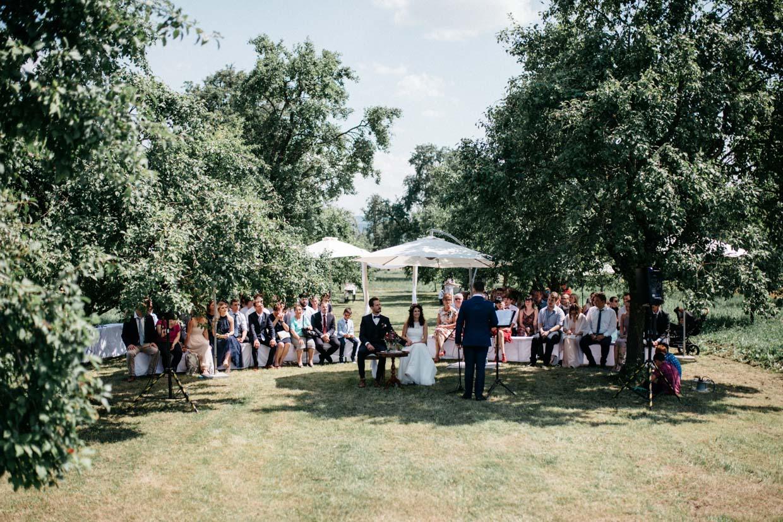 Brautpaar und Hochzeitsgesellschaft während der freien Trauung
