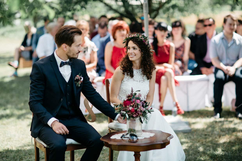 Brautpaar schaut sich während der freien Trauung an und lacht