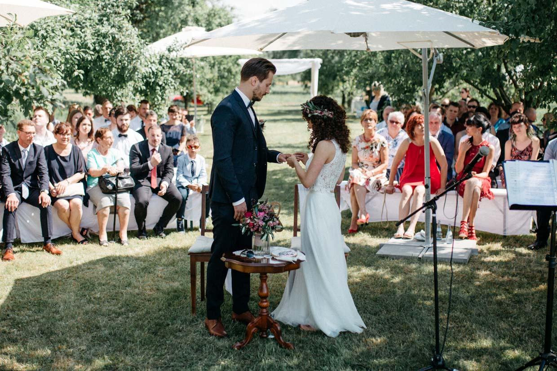 Braut steckt dem Bräutigam den Ehering an