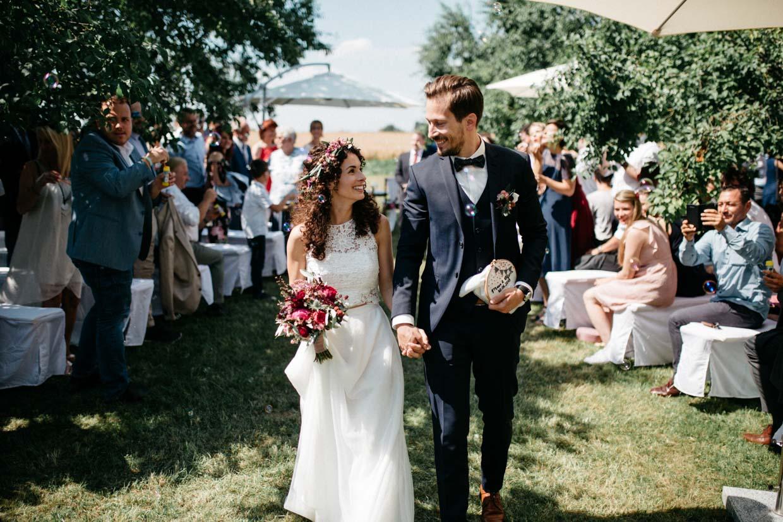 Brautpaar zieht glücklich nach der freien Trauung aus