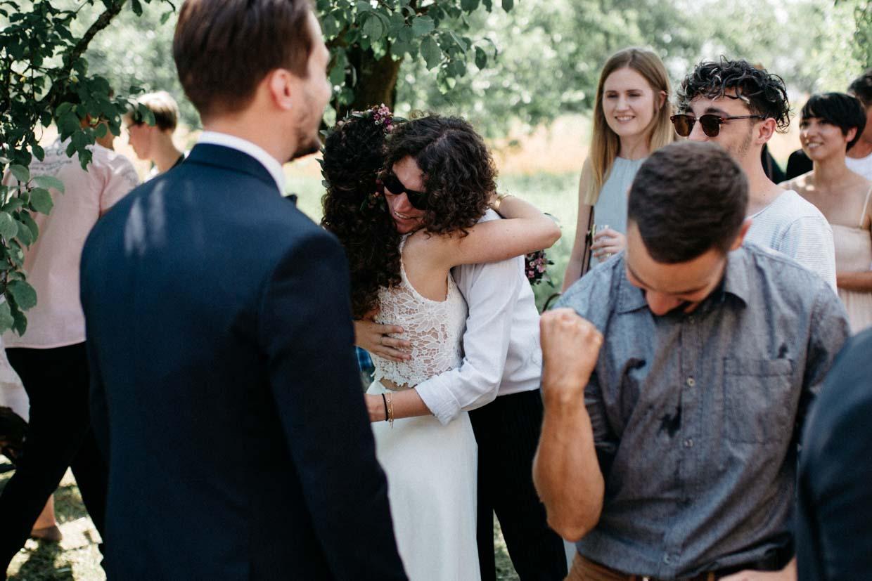 Hochzeitsgast umart die Braut und anderer Hochzeitsgast freut sich mit dem Bräutigam