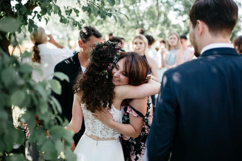 Hochzeitsgast umarmt die Braut beim Gratulieren