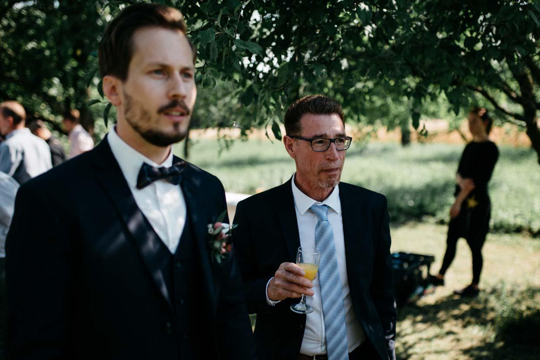 Bräutigam und Brautvater schauen gespannt beim Sektempfang