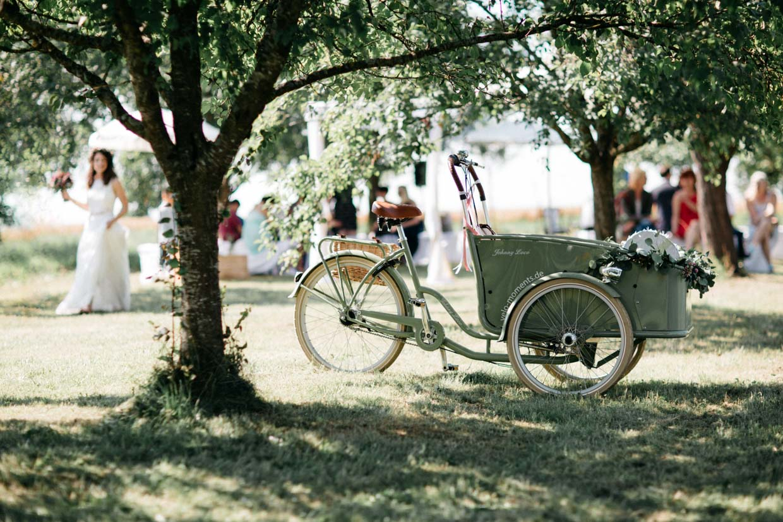 Altes Fahrrad mit Sitzkorb und Braut im Hintergrund