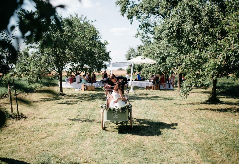 Brautpaar fährt mit altem Fahrrad mit Sitzkorb und küsst sich dabei