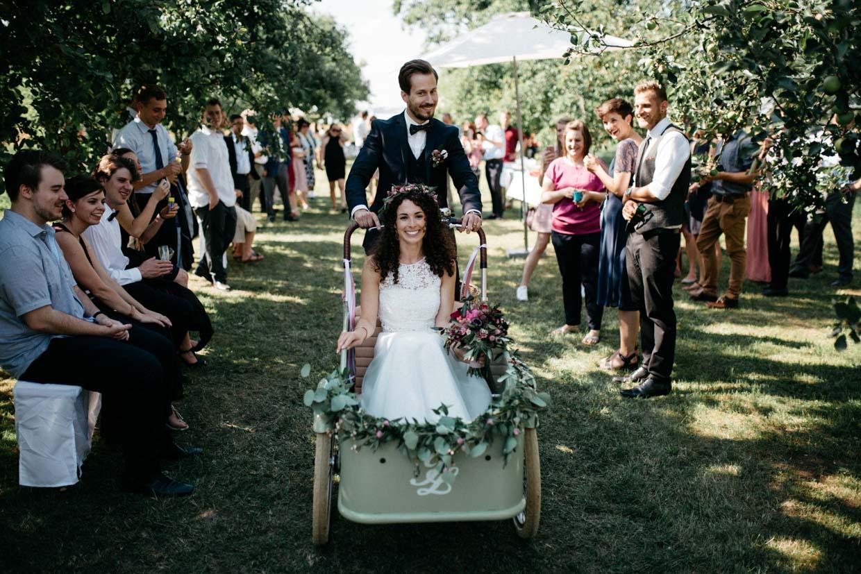 Brautpaar fährt mit altem Fahrrad mit Sitzkorb an den Gästen vorbei